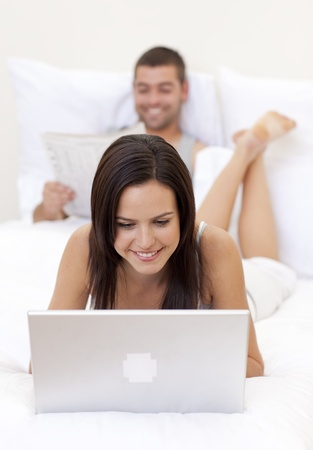 Woman using a laptop and man reading a newspaper photo