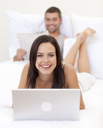 Smiling woman using a laptop and man reading a newspaper photo