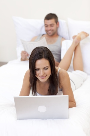 Couple in bed with a laptop and reading a newspaper photo