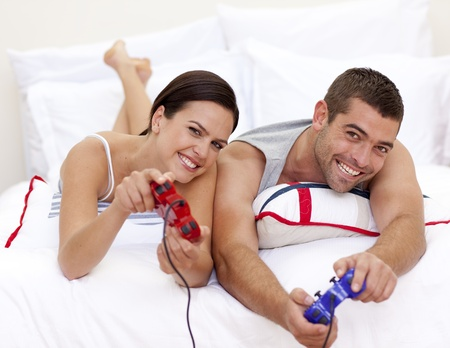 Couple playing videogames in bed photo