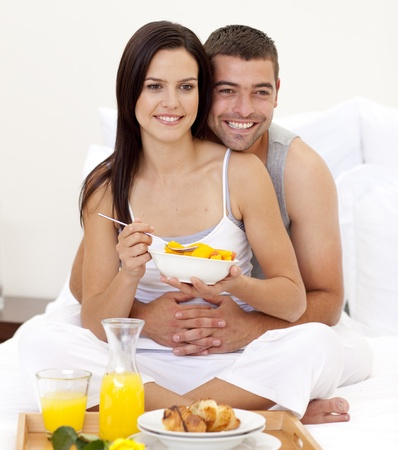 roomservice: Wife and husband having nutritive breakfast in bed Stock Photo