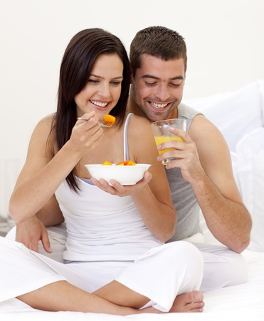 roomservice: Woman and man having nutritive breakfast in bed
