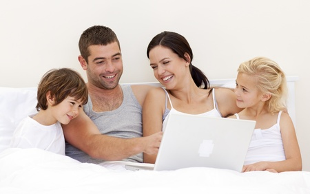 Parents and children using a laptop in bed Stock Photo - 10108996