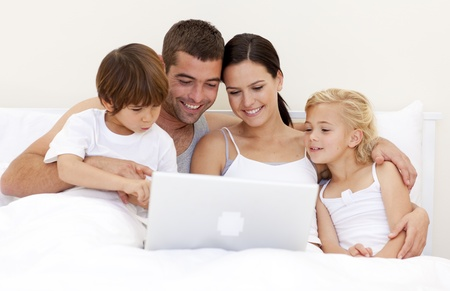 Family using a laptop in bed Stock Photo - 10110530
