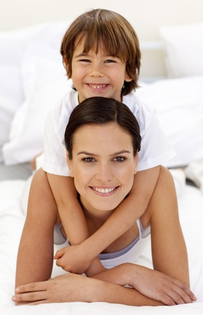 Son hugging his mother in bed photo