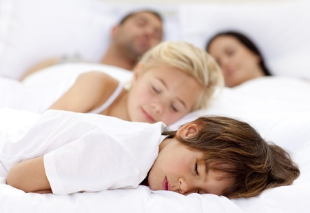 Children sleeping with his parents photo