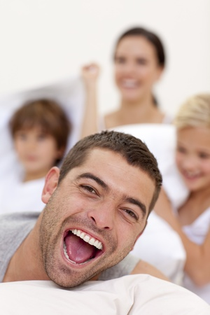 Portrait of laughing father playing with family in bed Stock Photo - 10111879
