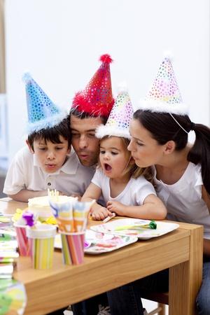 Niña sopla las velas en el día de su cumpleaños con la familia Foto de archivo - 10112456