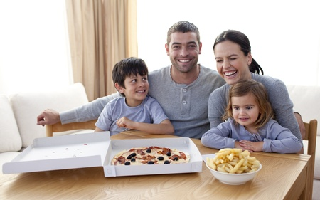 Family eating pizza and fries on a sofa photo