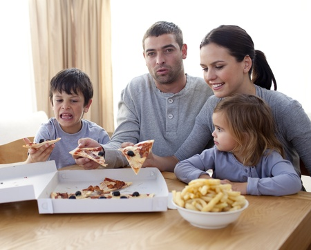 Parents and children eating pizza and fries on a sofa Stock Photo - 10111308