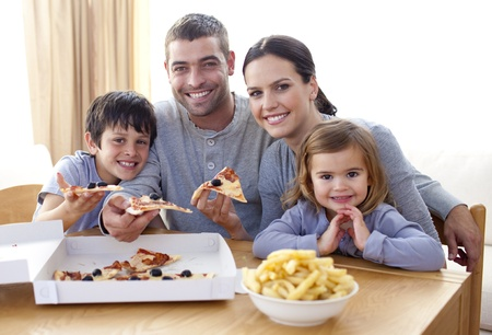 eating pizza: Parents and children eating pizza and fries at home