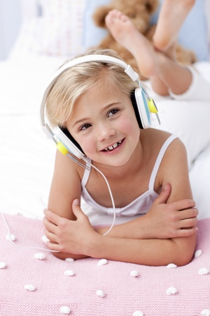 Little girl listening to the music in bed with headphones photo