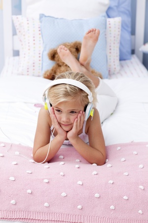 Little girl lying in bed listening to the music photo