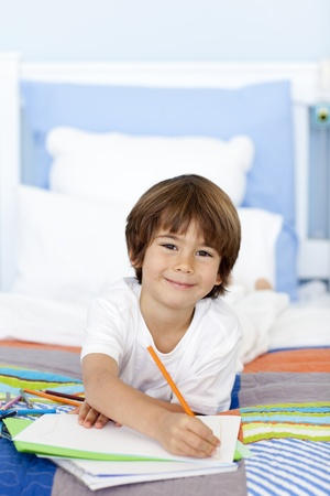 Smiling little boy drawing in bed photo