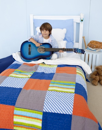 Little boy playing guitar in bedroom Stock Photo - 10112082