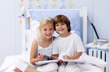 Enfants lire un livre dans la chambre à coucher Banque d'images