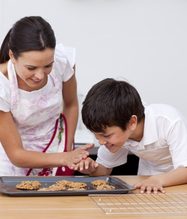 Mother and son baking biscuits in the kitchen photo