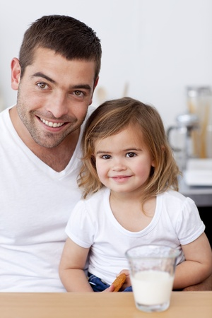 Smiling dad and little girl eating biscuits with milk photo