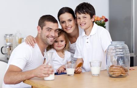 tomando leche: Familia feliz comiendo galletas y leche de consumo Foto de archivo