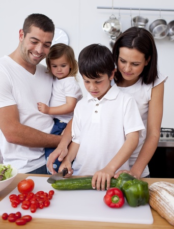 Little son preparing food with his family photo