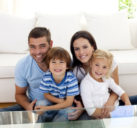 family on couch: Portrait of happy family smiling in living-room