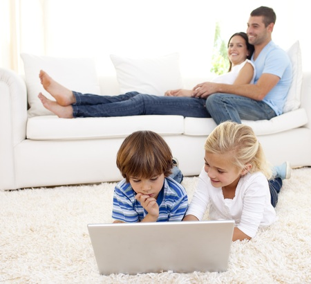 Children using a laptop and parents lying on sofa photo