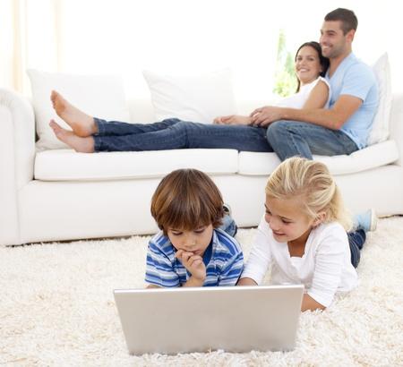 Kinder mit einem Laptop und Eltern auf Sofa liegend Lizenzfreie Bilder