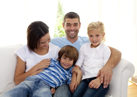 Playful family sitting on sofa at home photo