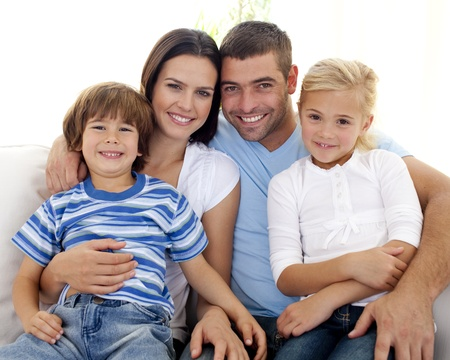 Happy family sitting on sofa at home photo