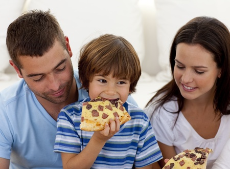 Happy boy eating pizza with ihs parents photo