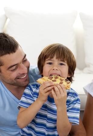 Boy eating pizza in living-room with his father Stock Photo - 10112127
