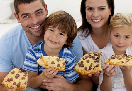 fast eat: Portrait of family eating pizza on sofa