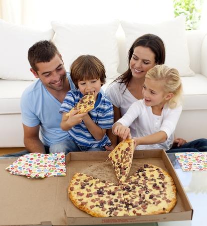 familia comiendo: Joven familia comiendo pizza en la sala de estar