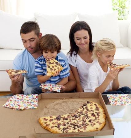 family eating: Familia comiendo pizza en la sala de estar Foto de archivo