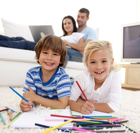 Smiling brother and sister painting in living-room Stock Photo - 10110903