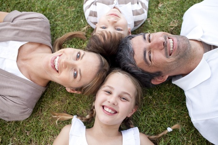 Smiling family lying outdoors photo