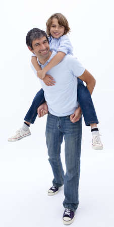 piggyback ride: Man giving boy piggyback ride Stock Photo