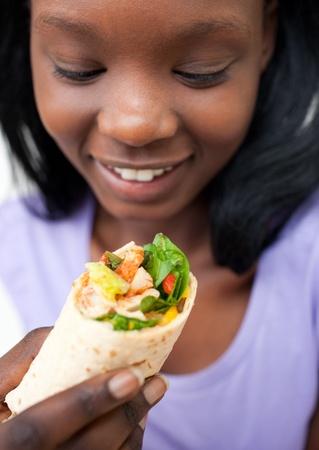 wraps: Afro-americano mujer joven comer una envoltura