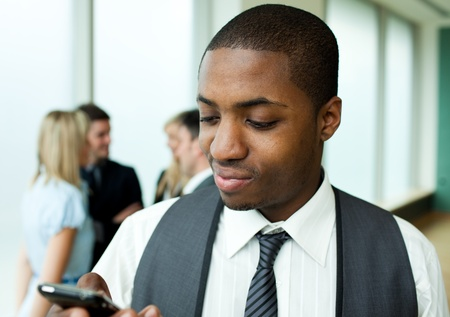 Afro-American businessman texting in office photo