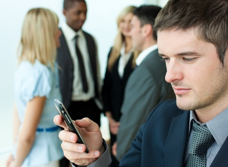 adult texting: Young businessman sending a text in office