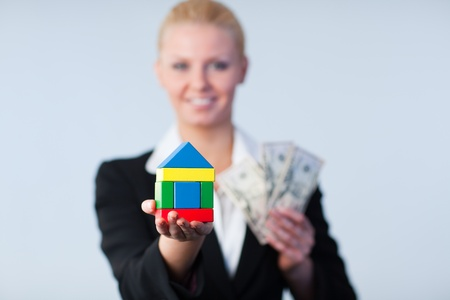 Businesswoman with house and dollars photo