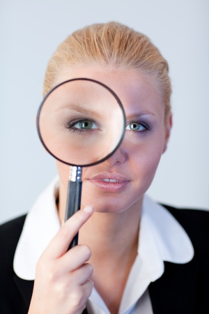 Serious Business woman looking through a magnifying Glass photo