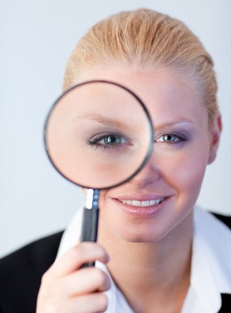 Smiling woman looking into a magniying glass photo