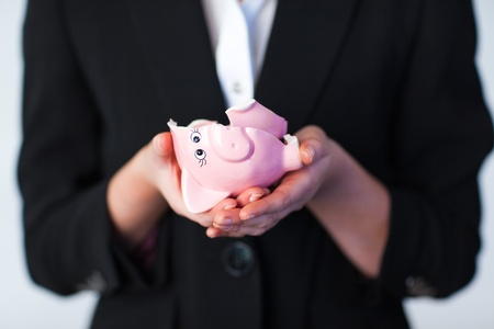 smashed: Business woman holding a broken piggy bank
