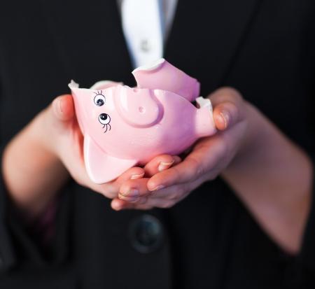 broken up: Business woman holding a broken piggy bank