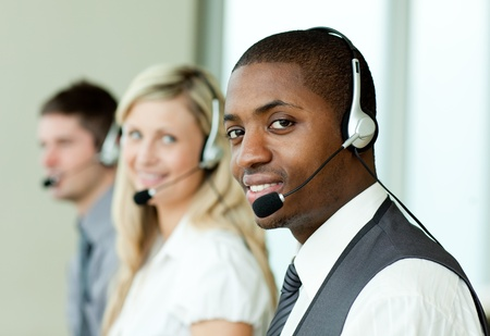 Businesspeople with headsets smiling at the camera photo