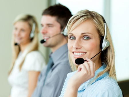 helpdesk: Three businesspeople working with headsets Stock Photo