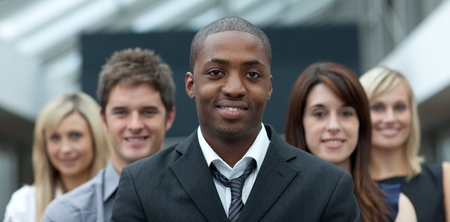 american staff: Afro-American businessman smiling at the camera with his team