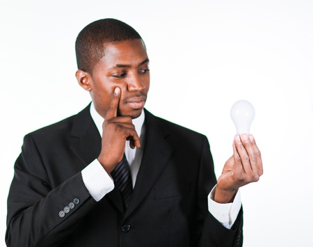 Thoughtful African businessman holding a light bulb Stock Photo - 10109532