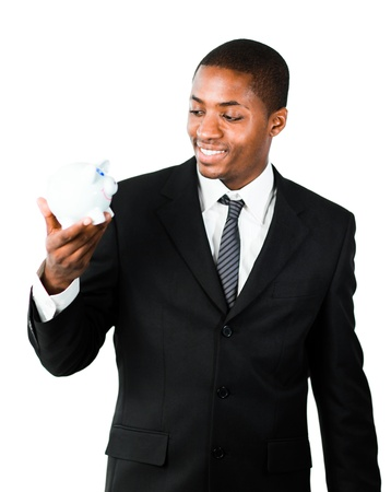 Young African businessman looking at a piggy bank photo